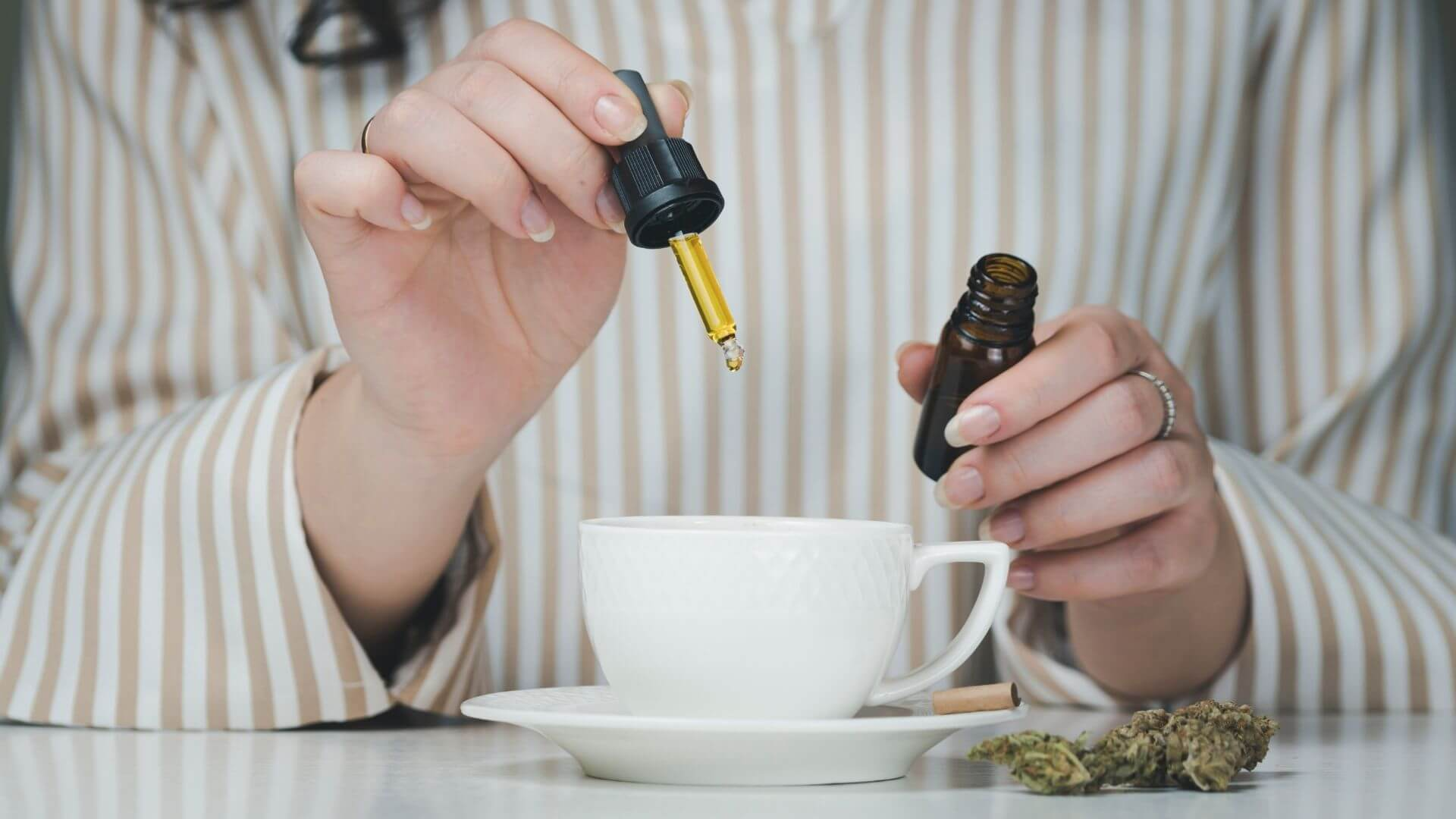CBD Oil dropping into a cup of coffee