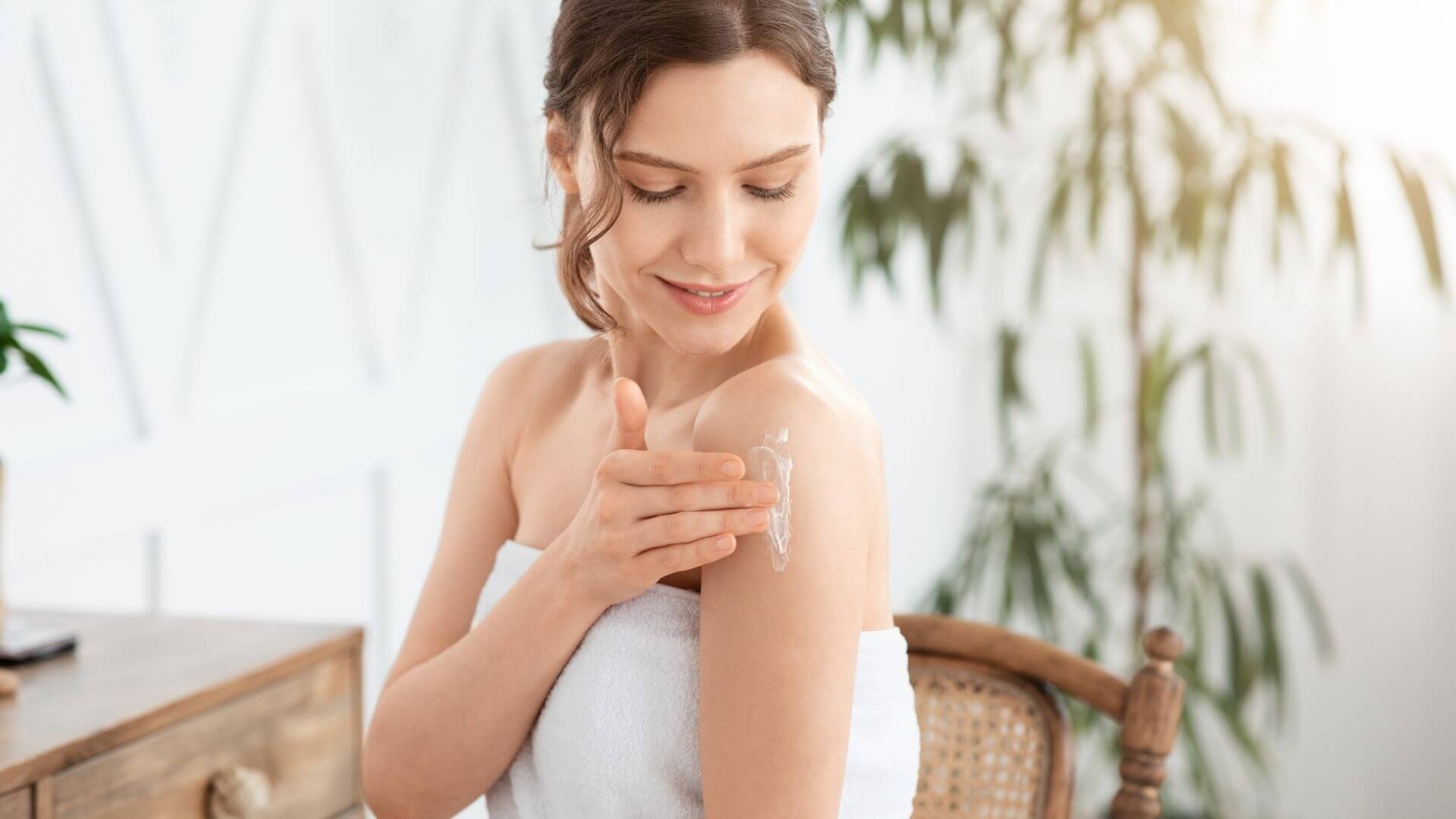 Woman in towel rubbing CBD Topical on her arm.